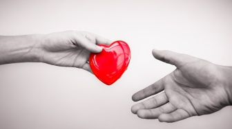 one hand gives a red heart to another hand