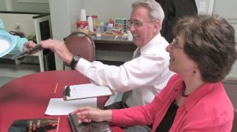 man and woman sitting at a table for book signing